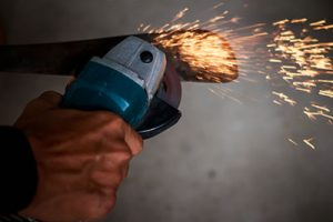 A worker cutting metal with a knife