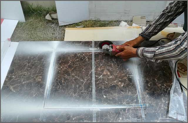 Man Worker cutting a tile using an angle grinder close up