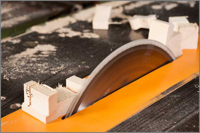 Image of a table saw blade in action in a woodworking workshop