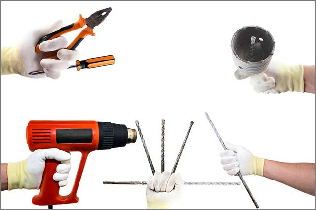 Different construction tools in the hands in white gloves