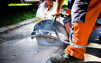 A construction worker creating slabs with a concrete saw