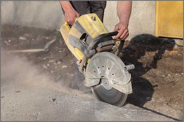 Shows a worker using a blade to go through concrete
