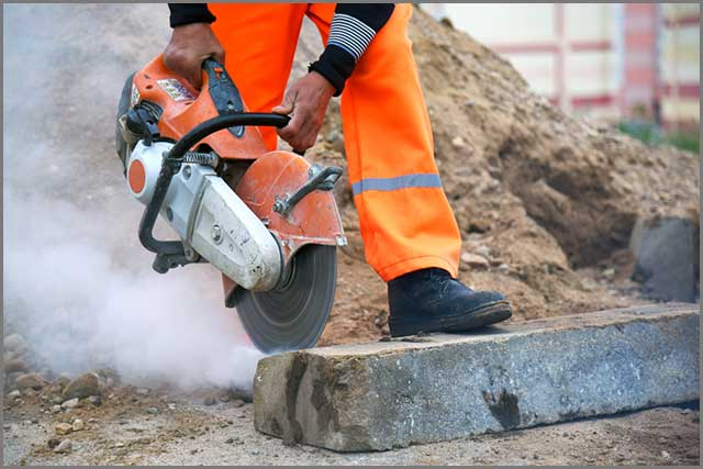 A construction worker cutting through concrete with a hand-held concrete saw