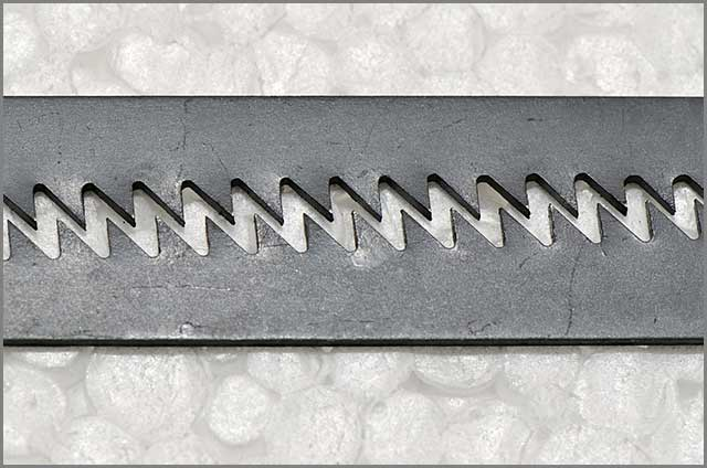 Image of two reciprocating saw blades lying together with the teeth facing one another