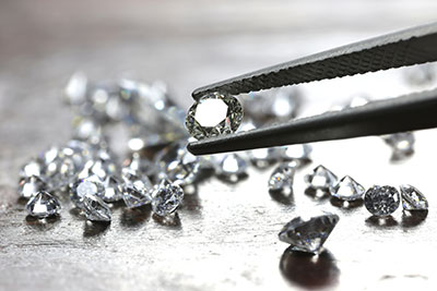 A brilliant-cut diamond held firmly by a tweezer