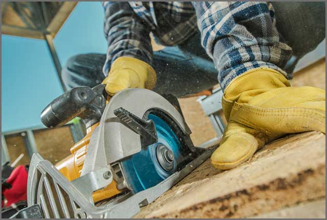 A construction worker cutting plywood with a circular saw