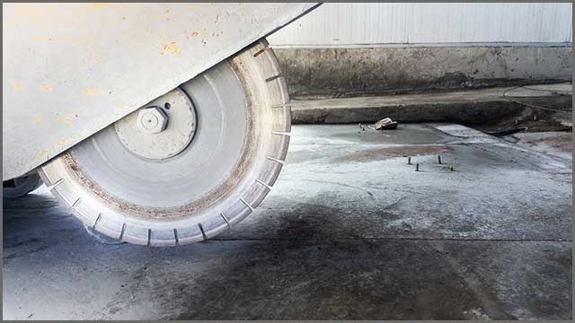 A diamond saw machine cutting through a concrete floor