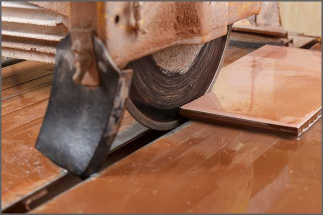 Image of a tile saw blade cutting a ceramic tile.