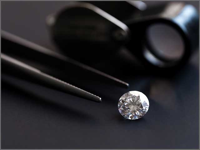 A diamond with tweezers and a magnifying glass