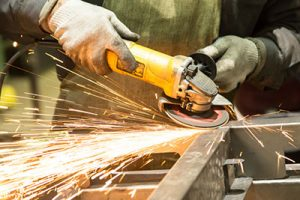 A worker cutting through metal with a hand-held angle grinder
