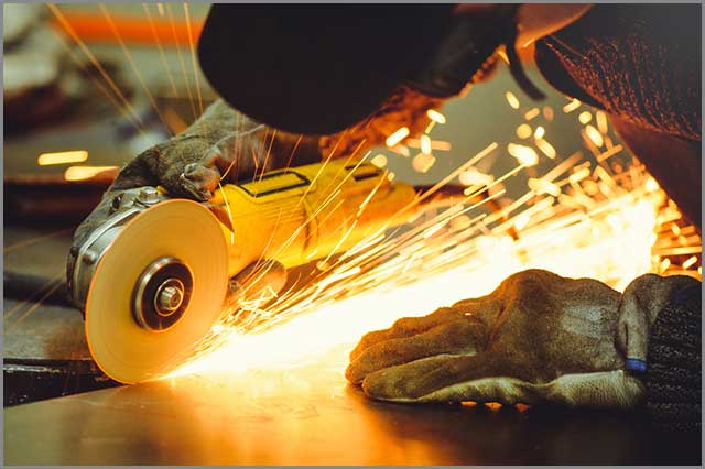 A worker cutting through hard material with a hand-held angle grinder