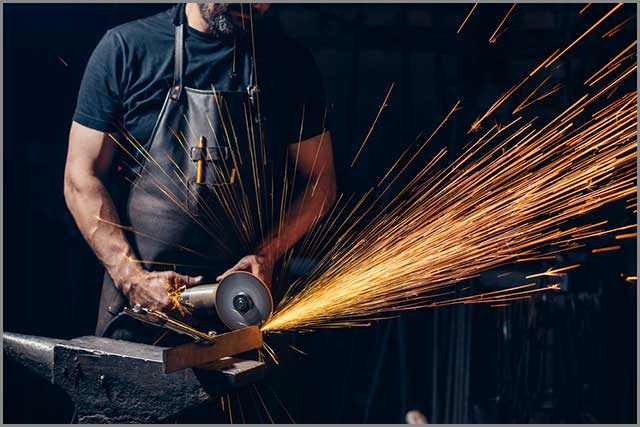 A worker using an angle grinder in a factory