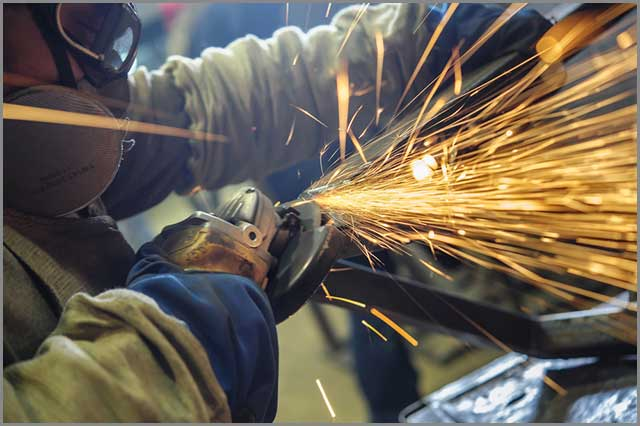 A worker welding seams with an angle grinder