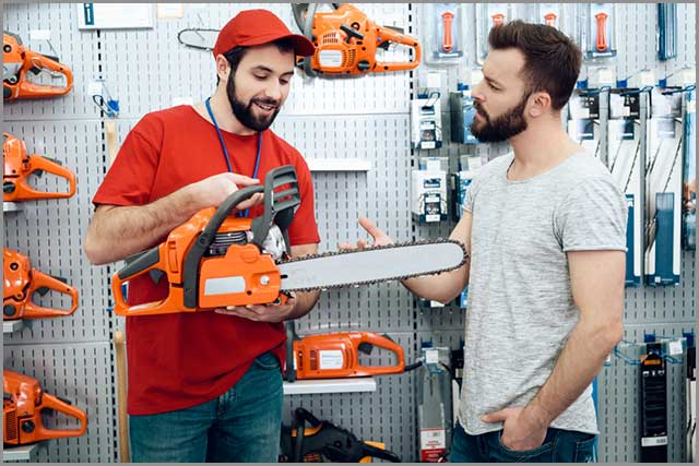 A salesperson showing a chainsaw to a customer
