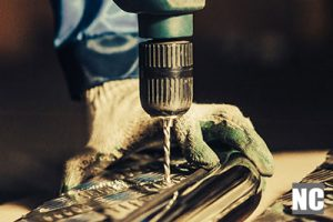 A workman drilling holes into a surface with a drill bit