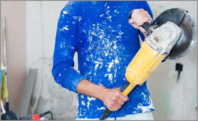 Construction worker holding a handheld concrete saw