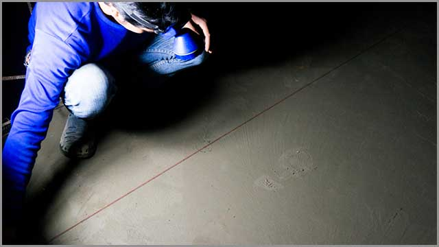 A worker making a chalk line on a concrete