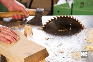 A carpenter working with a table saw to cut wood