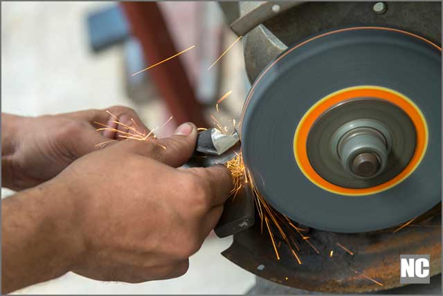 A machine operator dressing a grinding wheel with dressing too