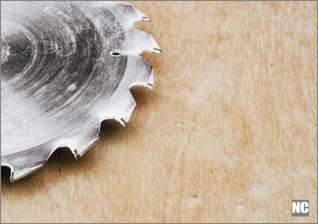 Polished blade surface resting on a polished plywood surface