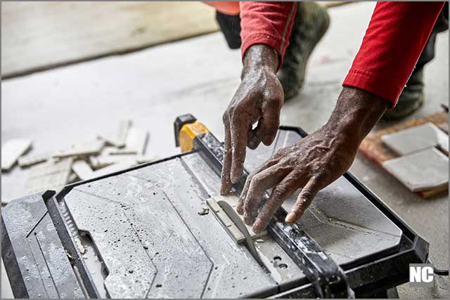 Close up of a man hands using a tile saw to cut ceramic tile