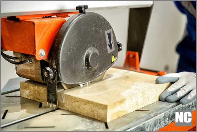 Worker cutting marble tiles using wet tile saw
