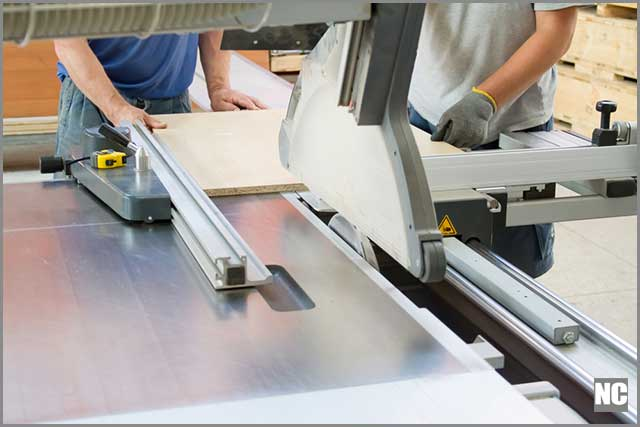 Men carefully handling the table saw during cutting.