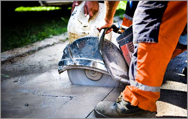Man operating wet-cutting concrete using a hand-held saw.