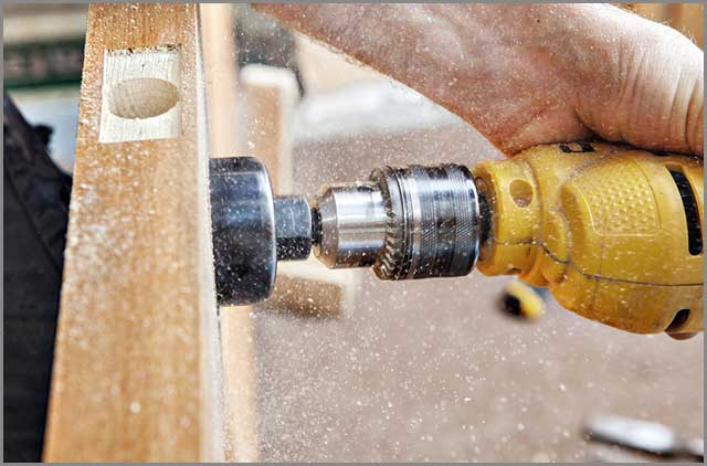 Drilling a big hole through the doorknob using an electric drill