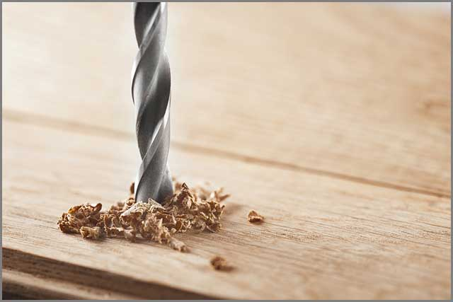 Use of drill bits to make a hole in wood