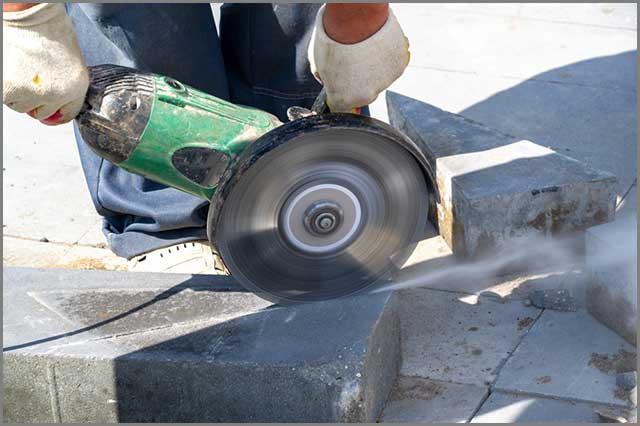 An electric saw cutting stone