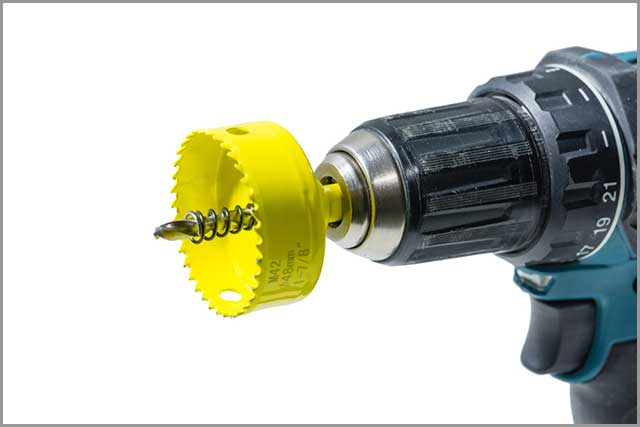 A Hole Saw Attached to a Hand-held Drill