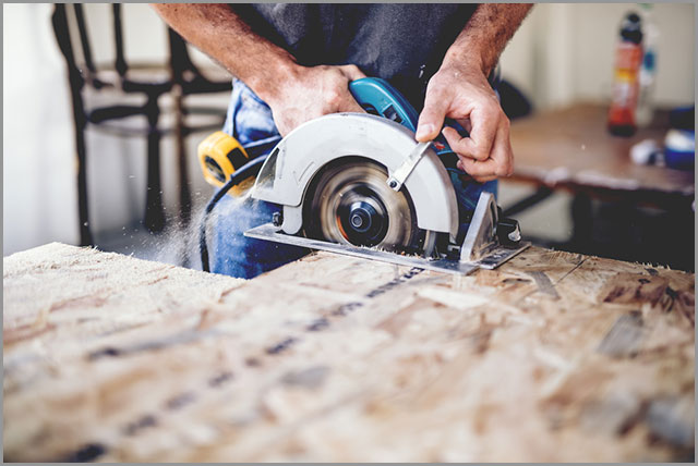 How to Cut Wood--A carpenter cutting wooden board with a circular saw