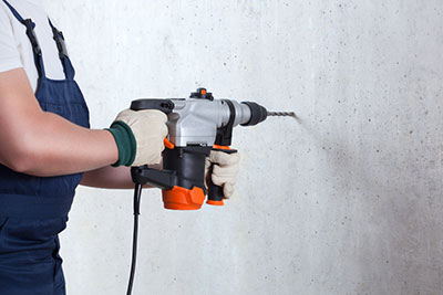 An operator holding a hammer drill